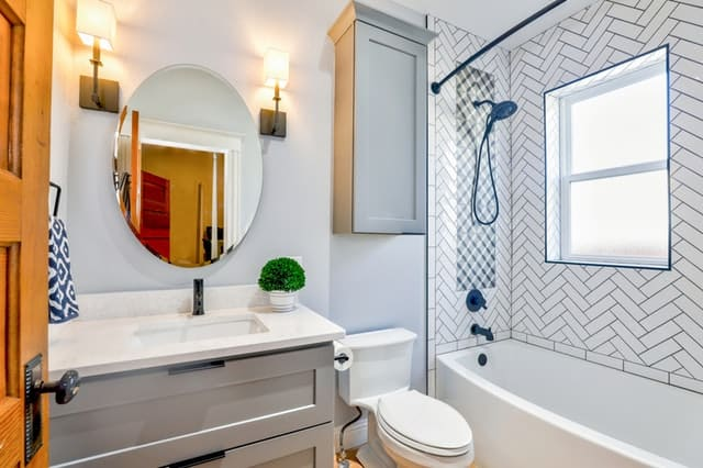 Clean white bathroom with sink, toilet and tub shower.
