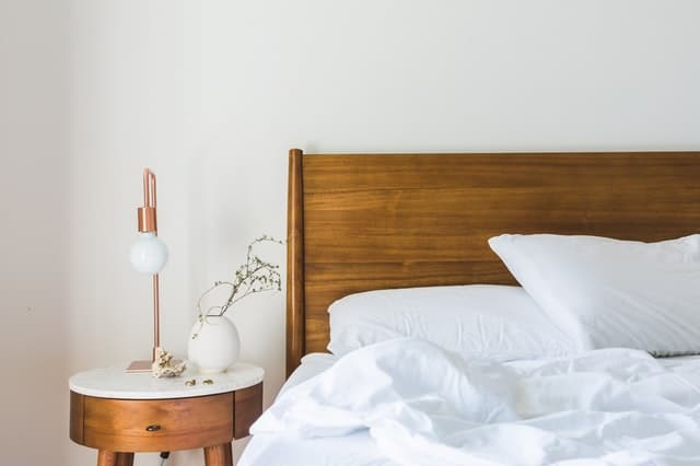 wood bed with white sheets and wood side table