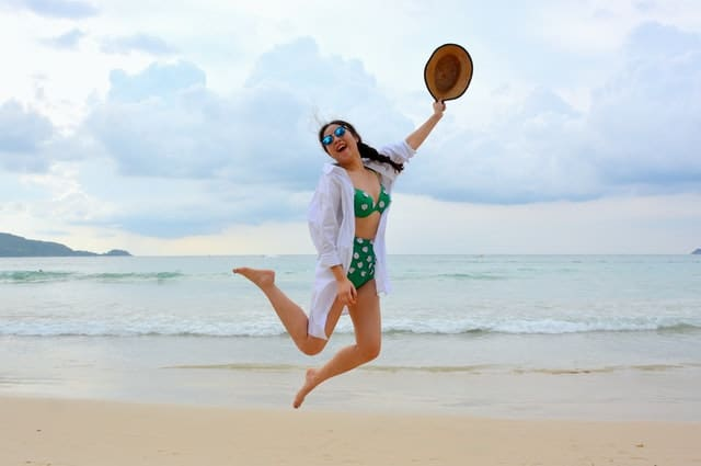 Happy woman at beach jumping