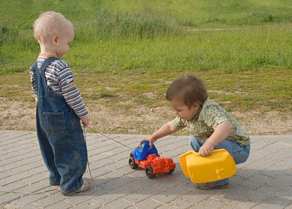 Little boys playing with trucks outside.
