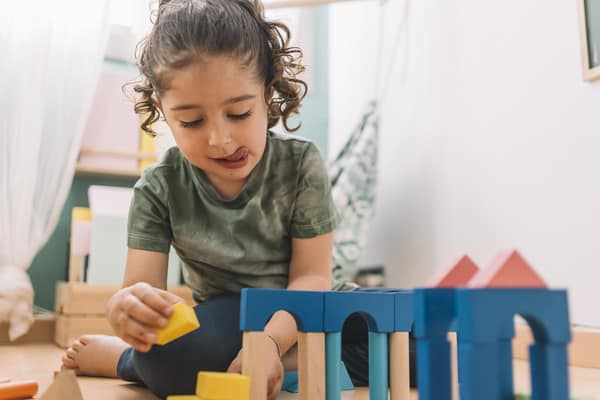 Little girl concentrating as she builds a wooden block tower.