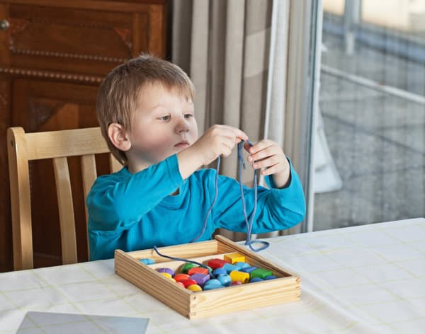 Little boy sitting at a table and threading wooden beads onto a shoe lace.