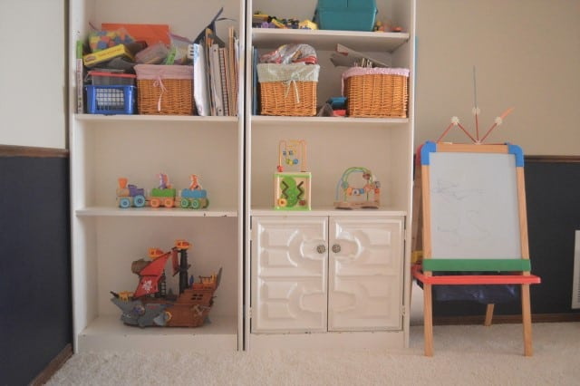 Toy organization - book shelf with pirate ship, baby toys, and a whole toy of kids' craft supplies.