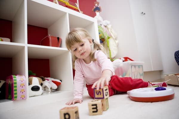 A little girl with blonde hair, stacking wooden blocks.