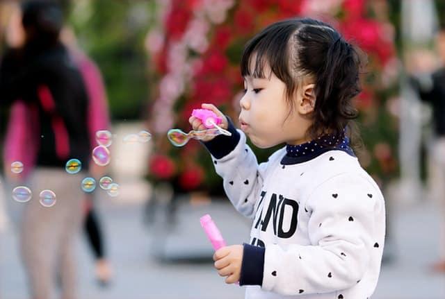 A cute little girl blowing bubbles outside.