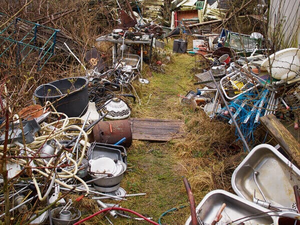 A grassy yard packed with junk scrap metal, sinks, bike handles, pots and pans. It's a mess. A similar yard is what caused me to start my decluttering journey.