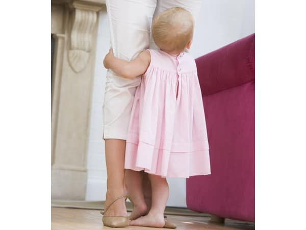 Young girl in a pink dress clinging to her mom's leg. | Meal planning greatly reduces stress at dinner time.