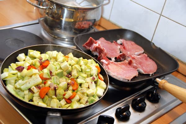 Stove top with chopped zucchini in one pan and pork chops in the other. | meal planning schedule
