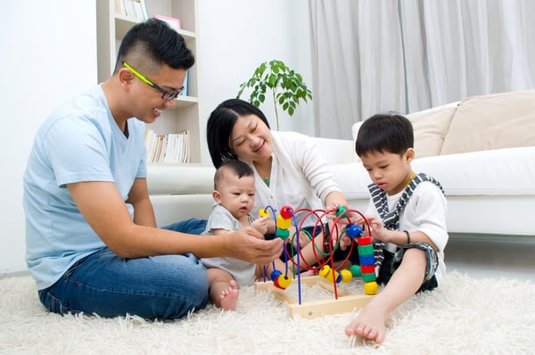 Family of mom, dad, baby and 3 year old son are sitting on the living room floor playing with one of those toys that has wooden blocks doing loopy loos on metal rods.