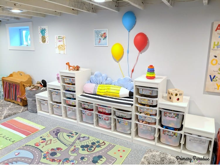 Martha stacked three different toy storage units together and created a bench in the middle. | Organizing the playroom
