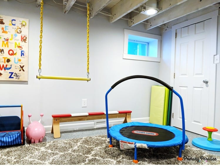 Martha created an indoor gym in their basement playroom by placing a mini-trampoline, balance beam and sit'n'spin in the space. She even hung a swinging bar from the rafters! | Playroom organization