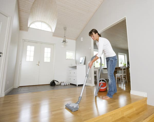 Mom vacuuming hardwood floors in entryway   Stay at home mom cleaning schedule