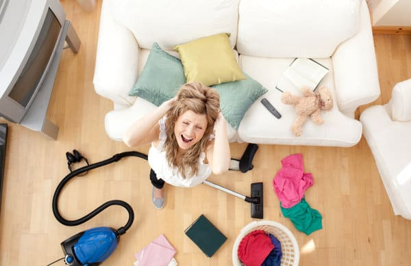 Top down view of a mom standing in the middle of a cluttered living room. She's gripping her hair and crying out in frustration. | Stay at home mom cleaning schedule