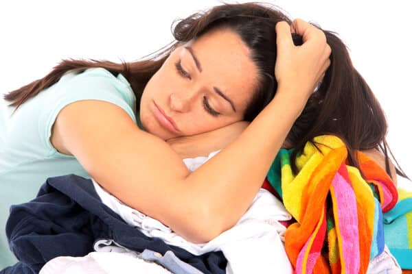 Exhausted mom resting her head on top of a pile of laundry. Is it clean? Anyone's guess!   Weekly cleaning routine for stay at home moms