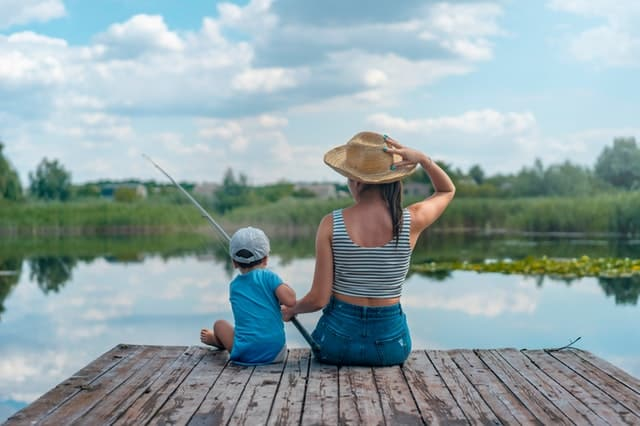 Picture of a mom wearing a hat, fishing while sitting on a dock with her toddler son.