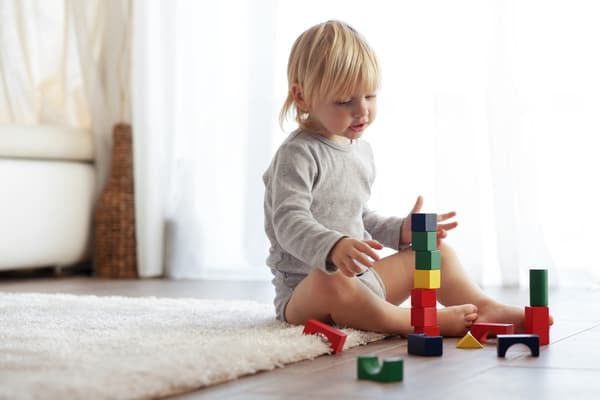 Little boy playing with wood blocks. This minimalist family doesn't struggle with too many toys!