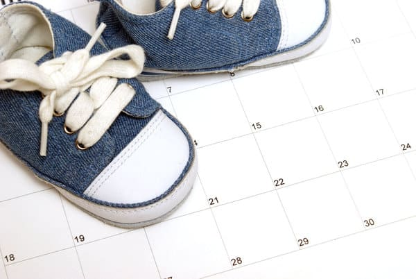 Blue baby sneaker sitting on top of a monthly calendar. | 3 year old schedule