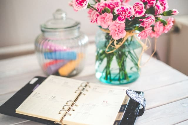 Planner open on a desk, with a vase of pink carnations behind it. | 3 year old schedule