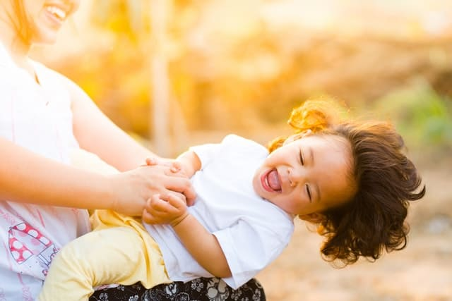 Mom dipping a small child on her lap, both mom and child are laughing. | 3 year old schedule