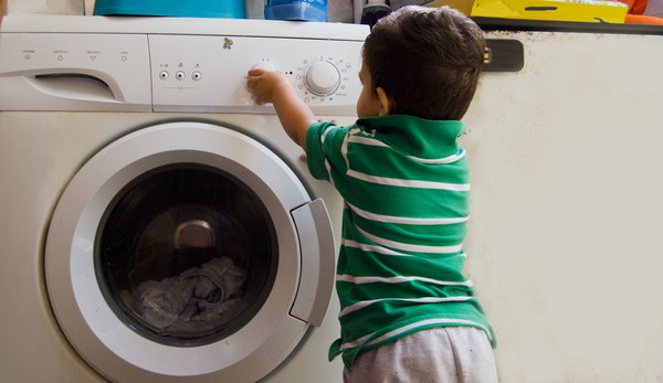 Toddler boy playing with the knobs on the front facing washing machine. | laundry routine