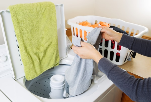 A woman puts laundry into the washer. | laundry routine