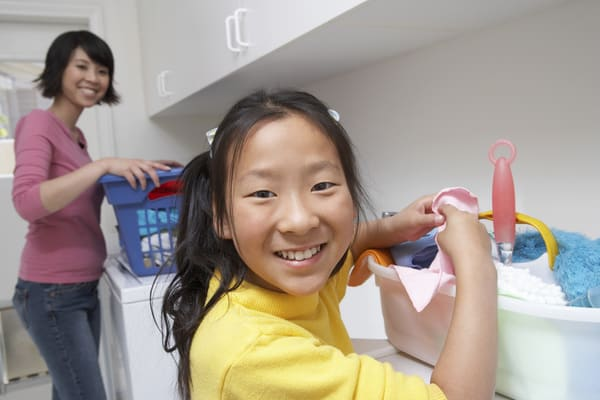 Girl and her mom folding laundry and smiling at the camera. | laundry schedule
