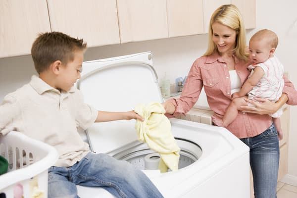 Mom holding a baby standing next to washer is putting laundry into the washer with 5 year old boy sitting on dryer. | laundry schedule