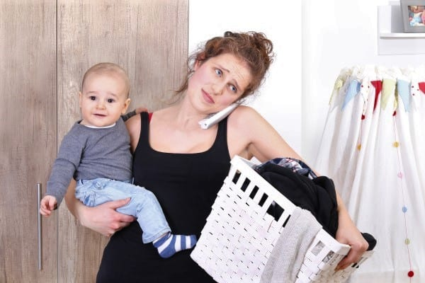 Stressed out mom on the phone while holding a baby on one hip and a laundry basket on the other. | stay at home mom schedule