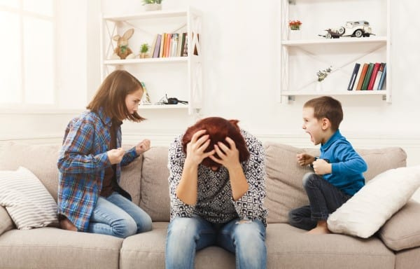 Frustrated mom sitting on couch with head in her hands. Her daughter on the left and her son on the right are fighting with mom in the middle. | Easy Activities for Kids