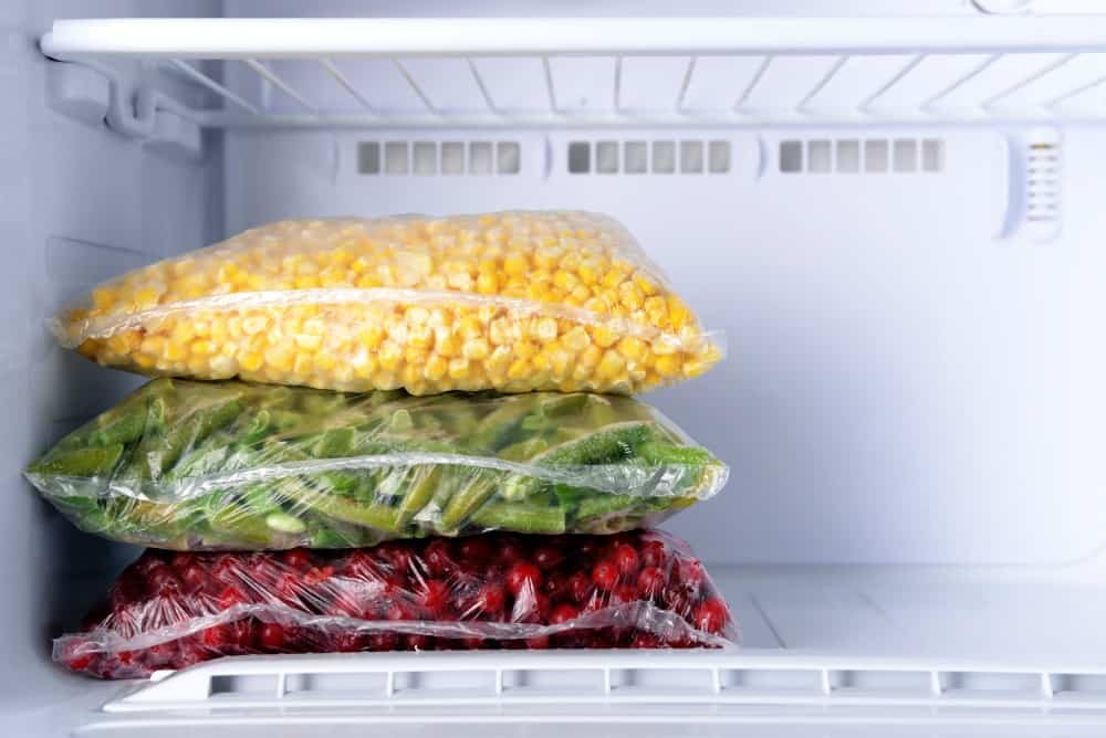 Gallon sized bags of corn, green beans and cranberries carefully stacked in the freezer. | freezer inventory