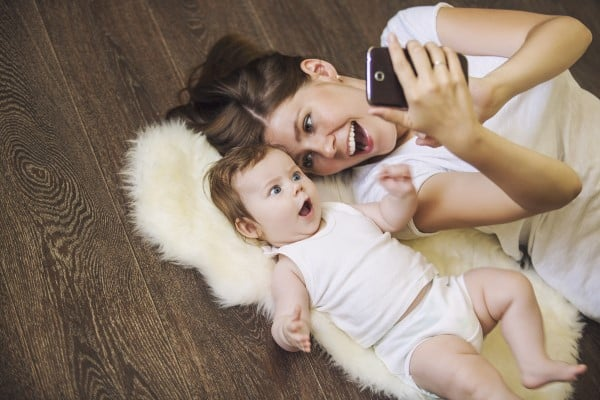 Mom and baby laying on the floor looking at a cell phone. The baby looks utterly shocked. | apps for moms