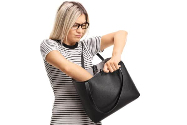 Frustrated woman rummaging through her large black handbag. | apps for moms