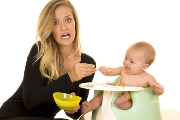 Stressed out mom spoon feeding her baby. | Best planners for moms