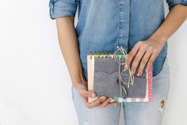 Woman holding a planner and glasses   best planner for moms