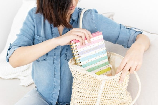 Woman putting planner into a big hand bag. | best planner for mom