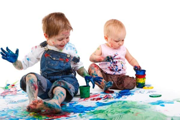 A young boy and a toddler girl finger painting on the floor. They're covered in paint. | tidy home