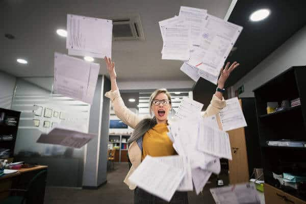 Frustrated woman in work office throwing papers into air. | declutter home office