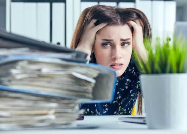 Woman stressed out and looking a giant stack of paper to declutter.