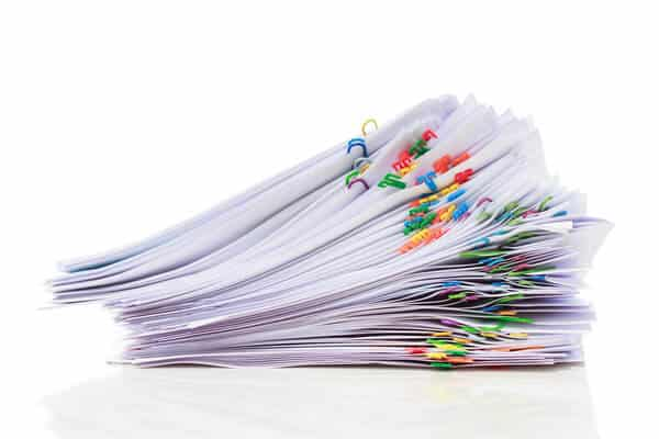 Stack of papers to declutter with colorful paper clips.