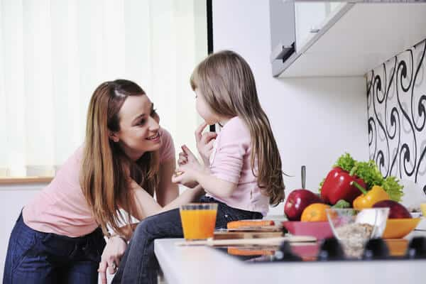 Mom smiling at her 4 year old daughter, who's sitting on the kitchen counter. Lots of fruits and veggies sit on the counter. | motivated mom