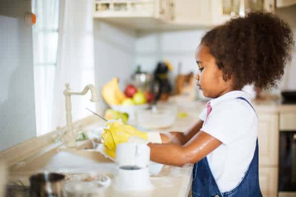 Little girl wearing yellow gloves and washing dishes. | sticker chore chart