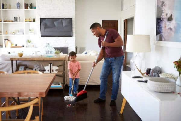 Little boy and his dad sweeping up the floor. | sticker chore chart