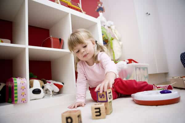 3 year old girl sitting on the playroom floor, stacking wooden blocks. | things to declutter