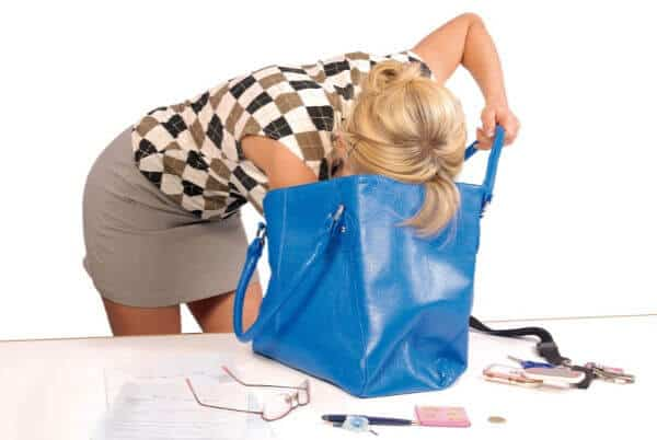 Woman head deep into her giant blue purse, frantically searching for her keys. | things to declutter