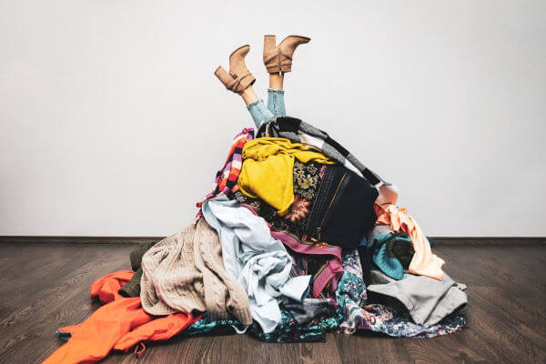 Humorous picture of a pile of clothes with woman's feet kicking out of it. |