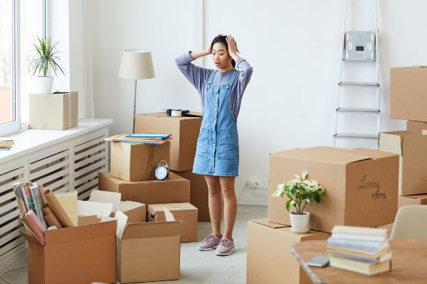 Woman surrounded by boxes. She has her hands on her head in exhaustion. | declutter house in 30 days