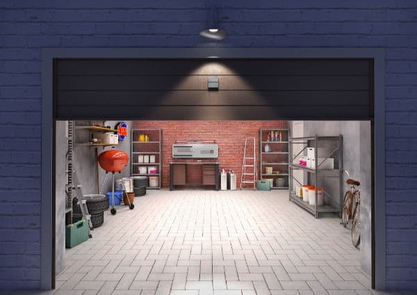 Looking at a clean and decluttered garage from the outside. Grill, tires, ladder, bicycle and workbench neatly line the walls of the garage.