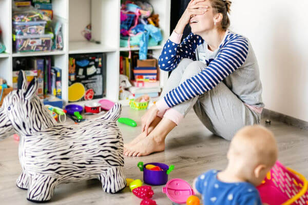 Mom sitting on floor surrounded by toys scattered on the floor. She has her hand covering her face in frustration. | decluttering blog