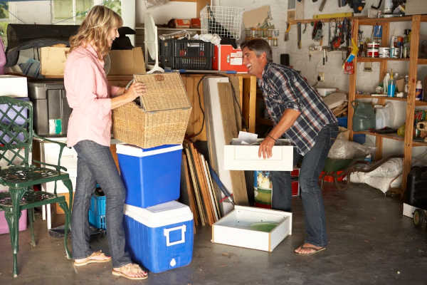 Woman and man going through boxes in a cluttered garage. | decluttering blog