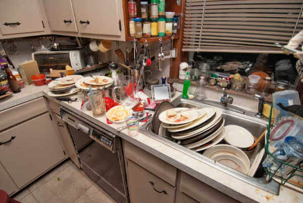 Messy kitchen with dirty dishes covering the kitchen and the sink. | decluttering method